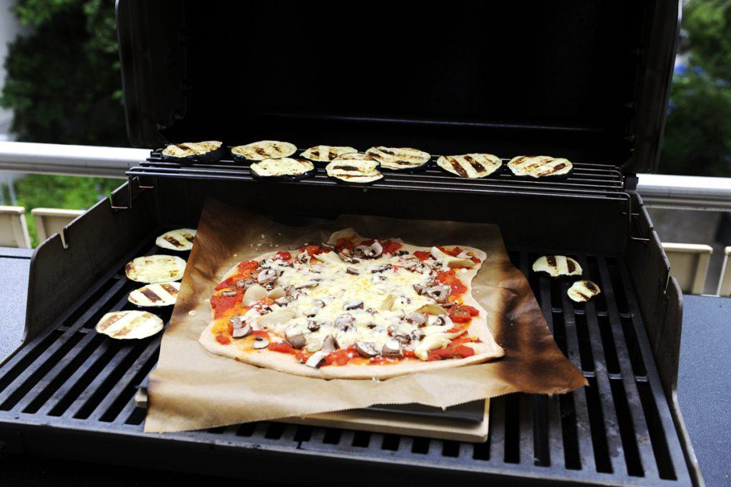 Pizza aus dem Grill mit Pizzastein, umrandet von Auberginenscheiben