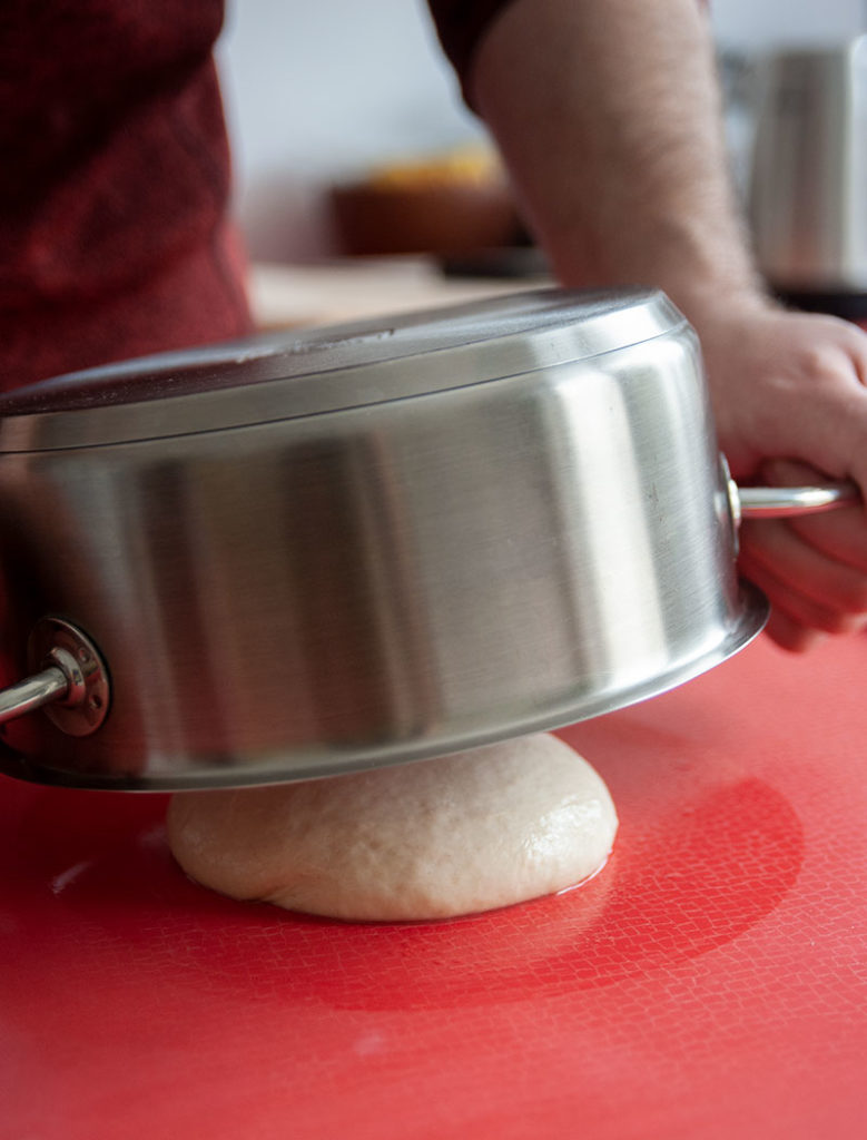 Tipp: Einen Topf mit kochendem Wasser ausspülen und diesen dann über den fertigen Strudelteig geben.